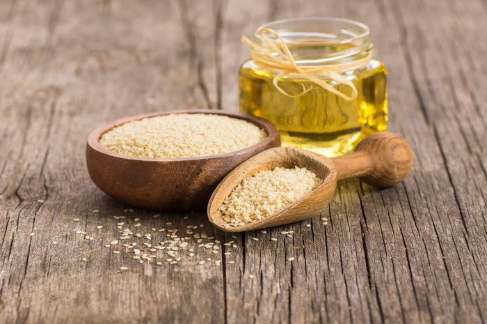 healthiest cooking oils | Glass bottle of sesame oil and raw sesame seeds