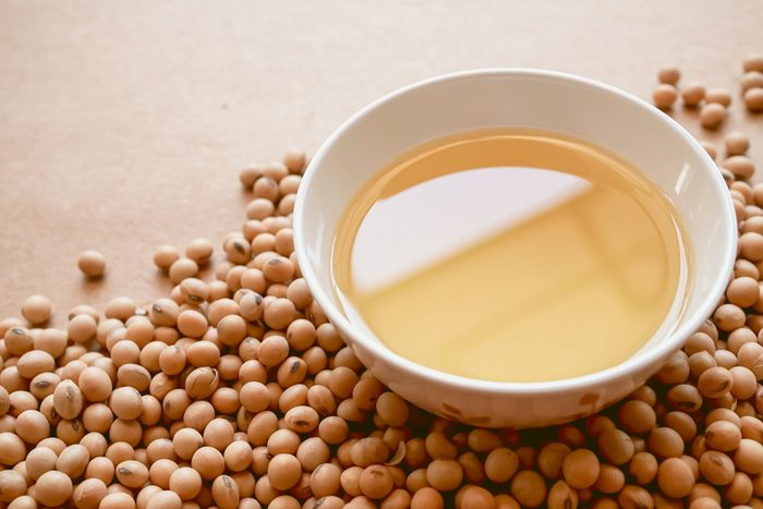 healthiest cooking oils | oil and soybeans on brown paper