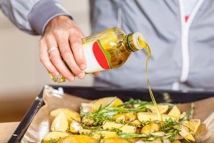 healthiest cooking oils | Pouring oil over potato wedges on baking tray