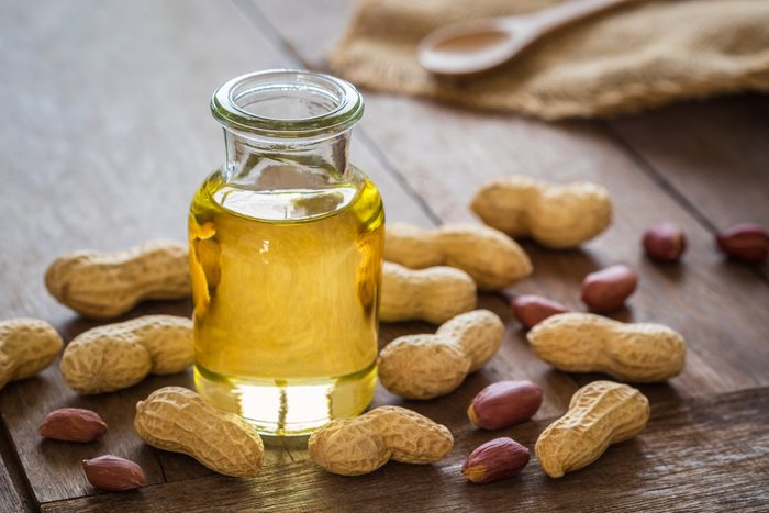 healthiest cooking oils | Peanut oil in glass bottle and peanuts