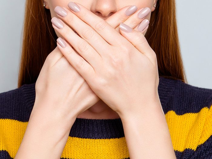 Halitosis   woman covering her mouth