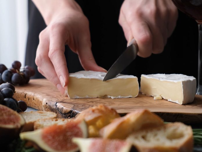 is cheese good for you | woman cutting cheese