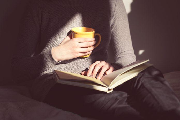 impact   woman holding mug and book   al etmanski