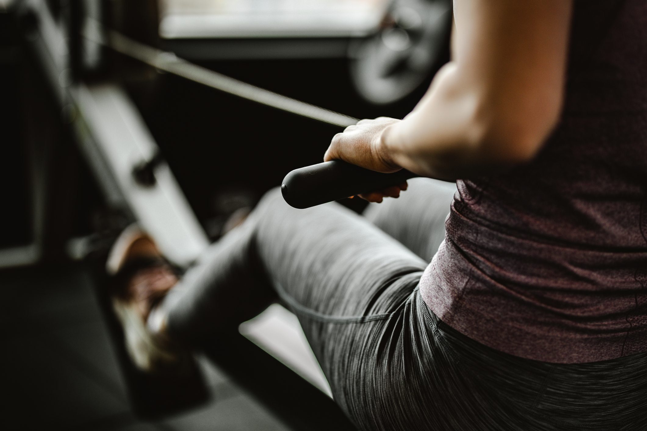 Close up of unrecognizable woman exercising on rowing machine in a gym.