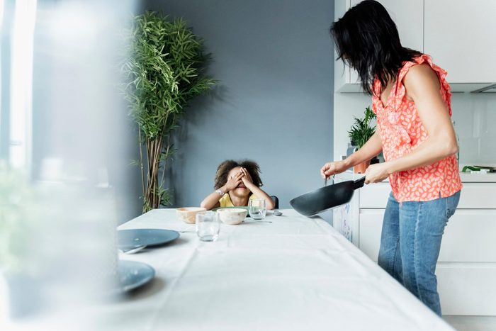 disordered eating triggers kids | Mother serving meal for daughter sitting at dining table