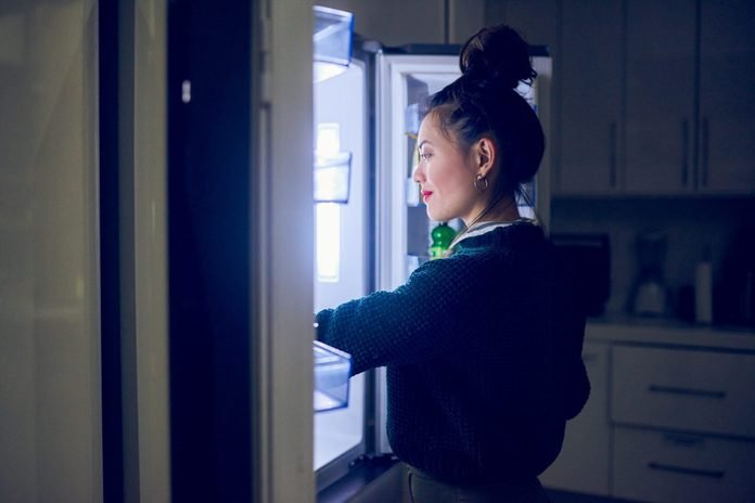 healthy late night snacks   woman opening the fridge at night