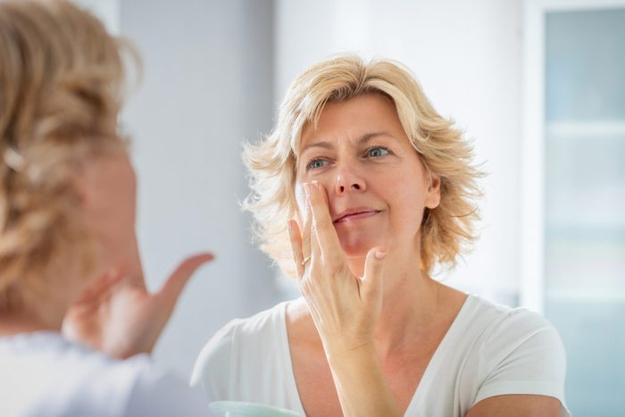 phymatous rosacea   woman looking in the mirror and touching face