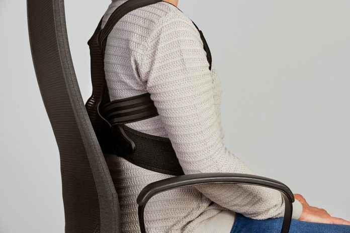 woman wearing a posture corrector in desk chair