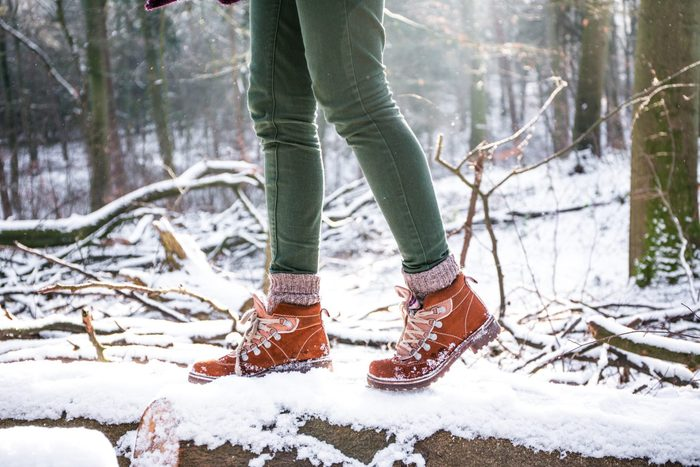 A woman hiking in the forest at the snowstorm