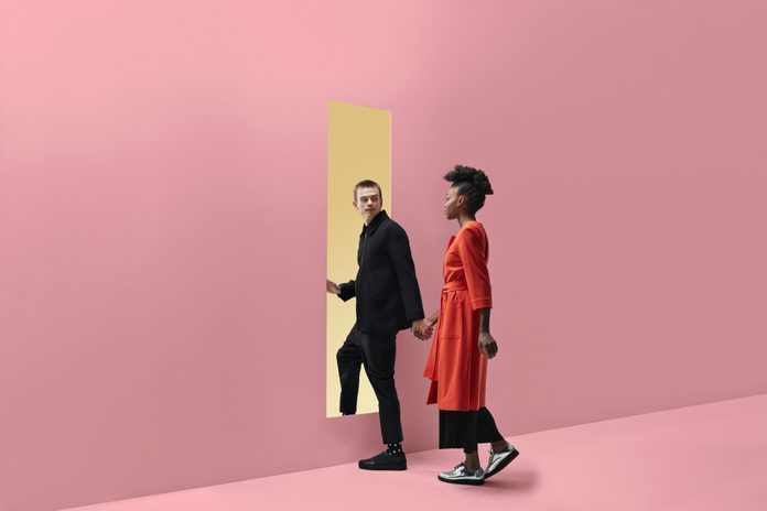 signs you're dating a narcissist   Woman & man holding hands, approaching rectangular opening in coloured wall