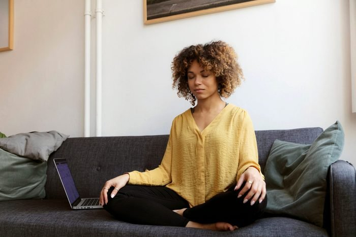 breathing exercises for anxiety   young woman sitting on couch at home doing breathing exercises