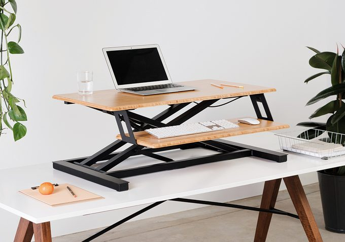 healthier home changes   desk riser on a table with laptop on it