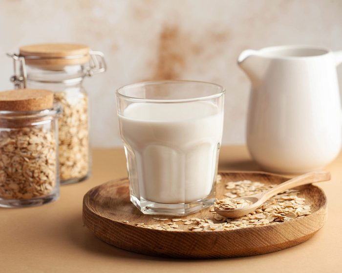is oat milk gluten free | Oat milk in a glass, flakes of baked cereals. Milk substitute, milk for vegetarians. Flatlay. Copy space.