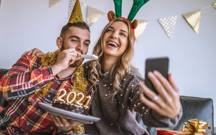 how to host a virtual new years party   Couple celebrating Christmas at home, holding chocolate cake with lit candles shaped as numbers 2021 and having a video call with friends