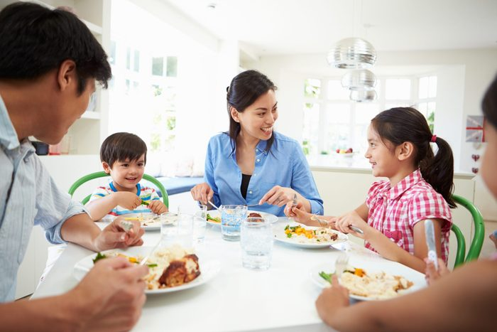 children healthy relationship with food | family talking and eating around a dinner table