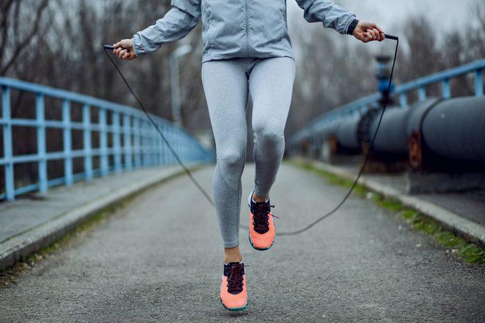 Unrecognizable Sportswoman Jumping Rope On A Bridge