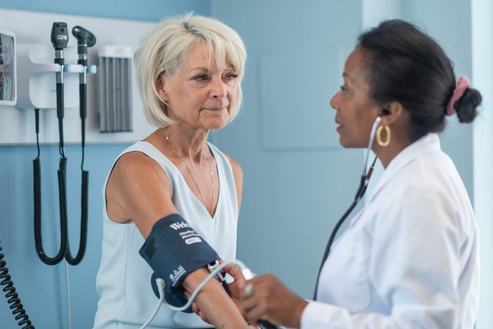 what causes heart disease   Mature adult woman in medical consultation with female doctor