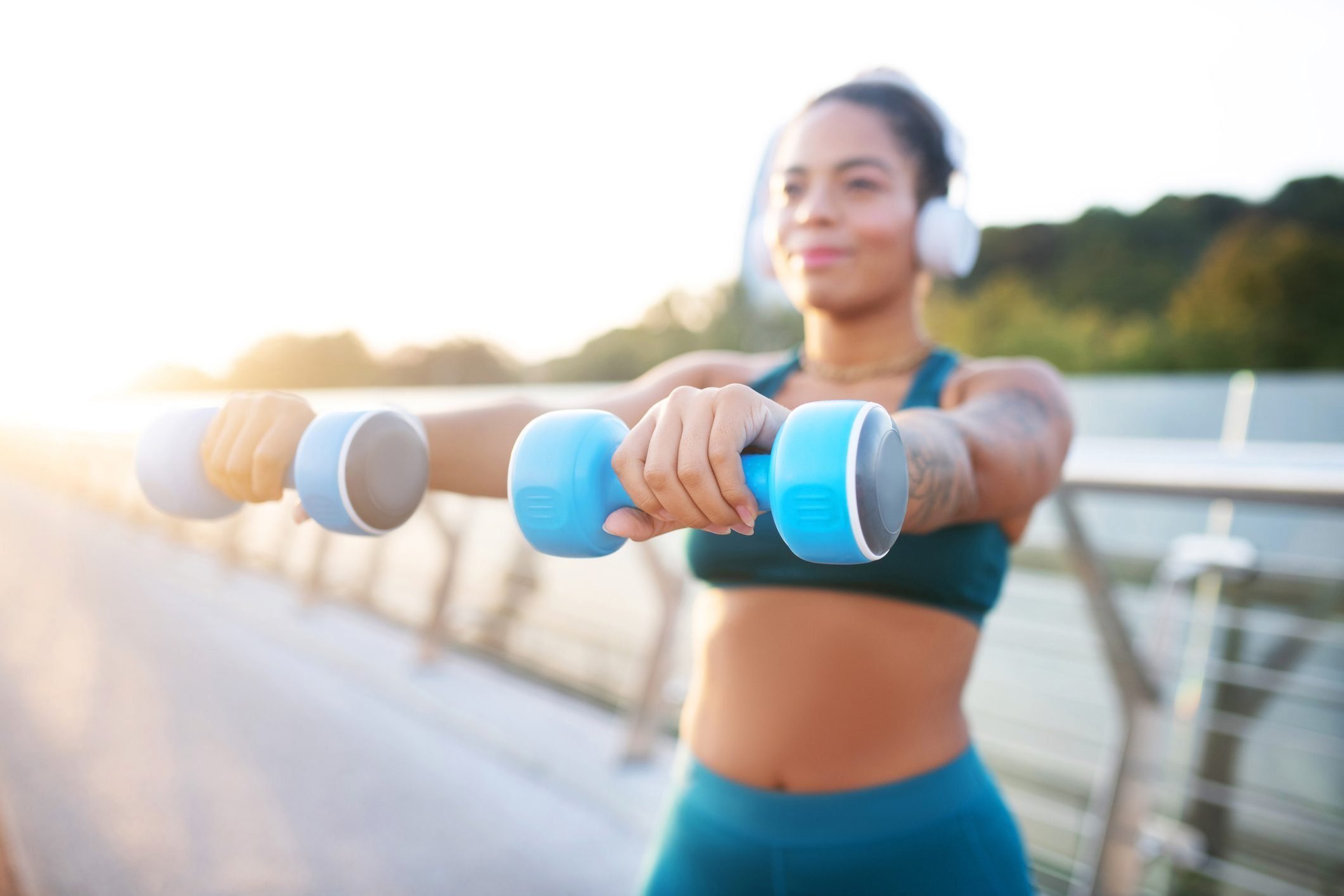 Woman holding blue barbells while building arm muscles