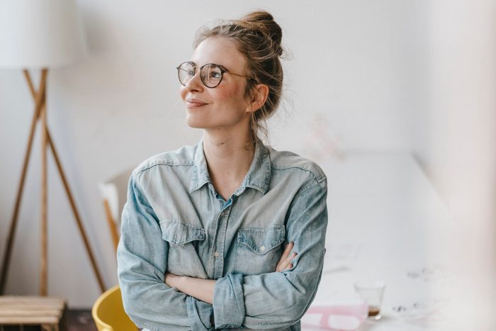 Smiling Young Woman In Office Looking Sideways