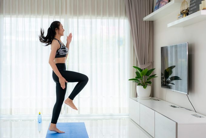 cardio workouts at home | Asian Woman Doing Strength Training Cardio Aerobic Dance Exercises U201chigh Kneeu201d While Watching Videos Fitness Workout Class Live Streaming Online On A Smart Tv In The Living Room At Home
