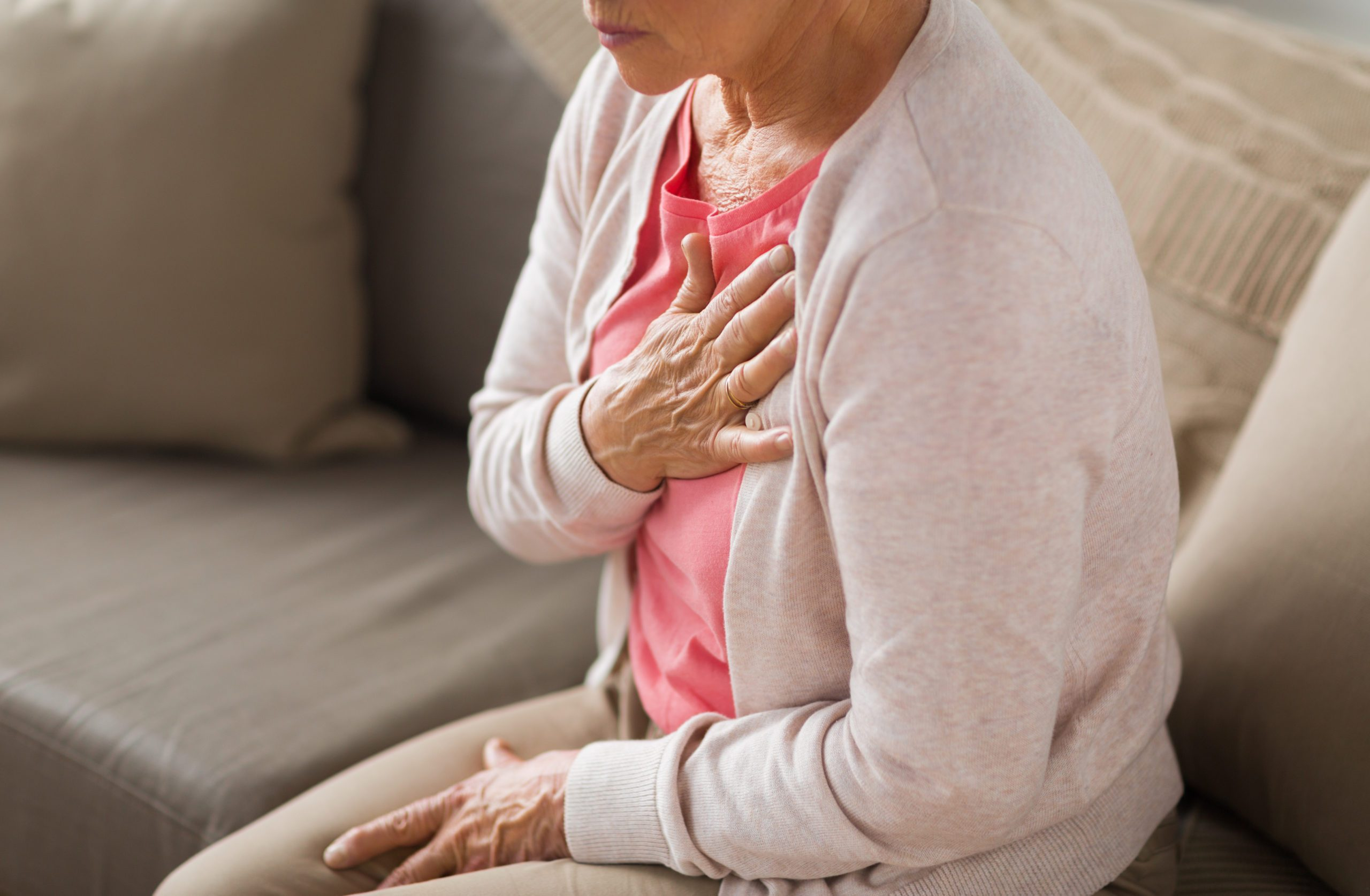 types of heart disease | woman clutching her heart