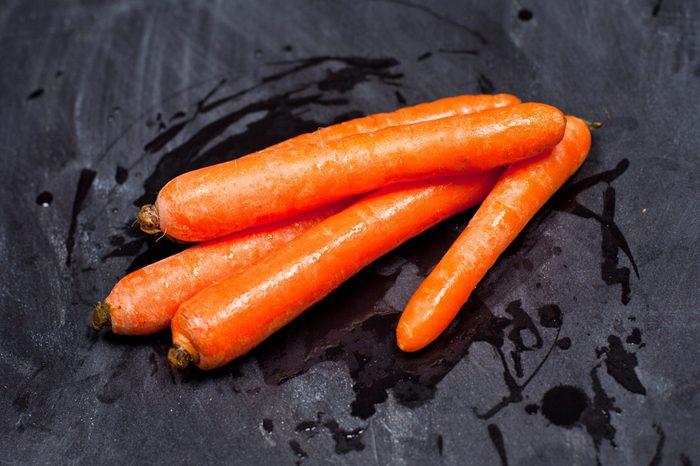 Fresh organic carrots on black background.
