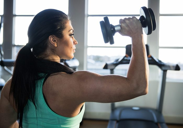 how to get stronger arms | strong woman ddoing a shoulder press with dumbbell
