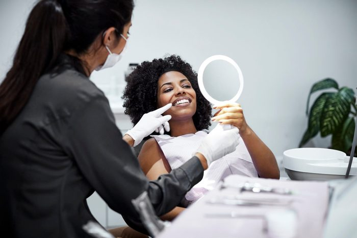 mamelon teeth | Patient Looking Teeth In Mirror At Dental Clinic