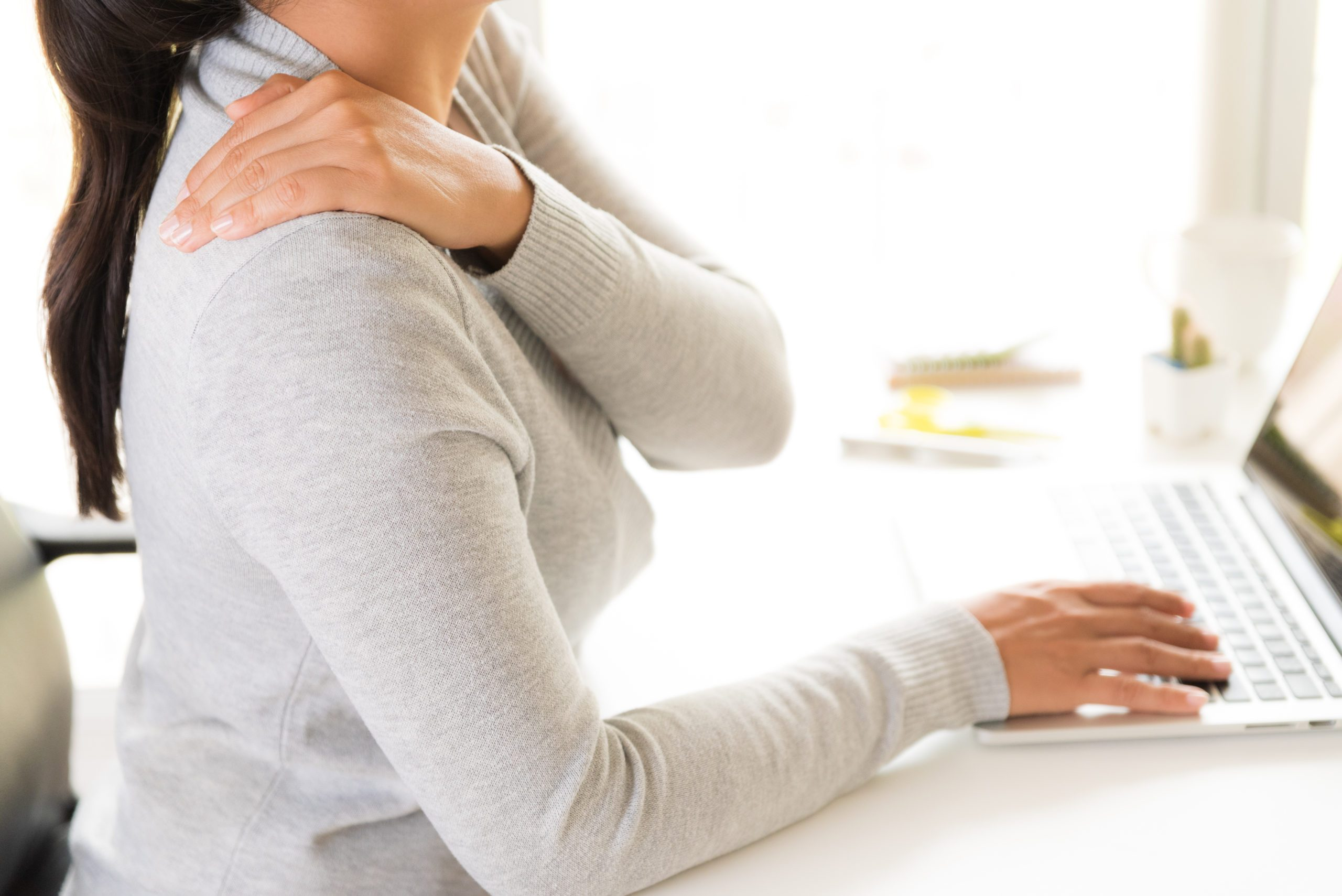 Closeup,woman,with,hands,holding,her,shoulder,pain.,office,syndrome