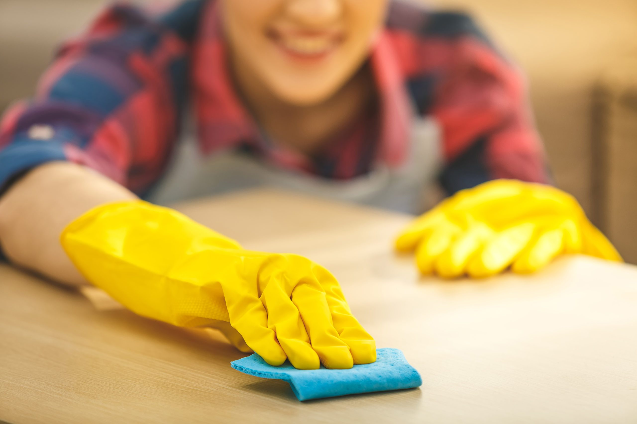 Woman,in,protective,gloves,is,smiling,and,wiping,dust,using