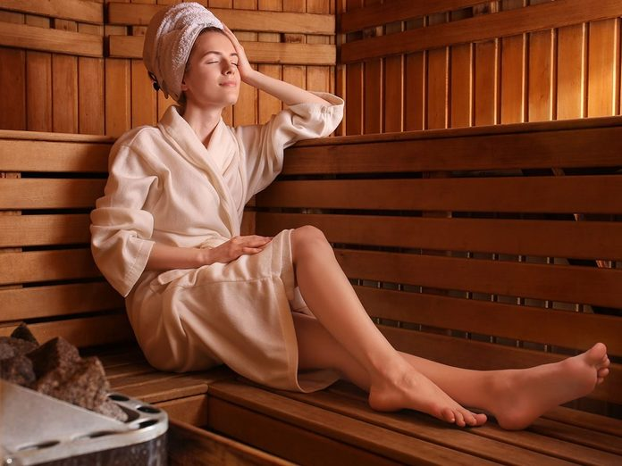 woman sitting on wooden bench in sauna.