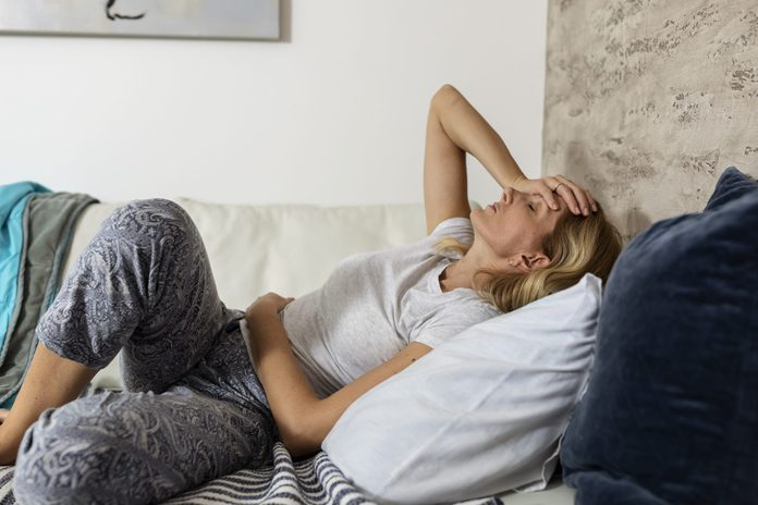 ulcerative colitis vs crohns disease   Mature Woman Lying On The Bed Suffering From Stomachache And Painful Period Cramps
