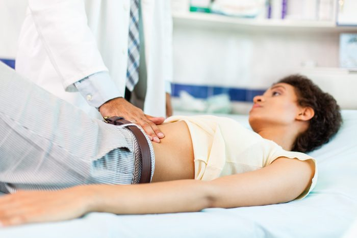 signs of colon cancer in women | Woman With Stomachache On Medical Exam