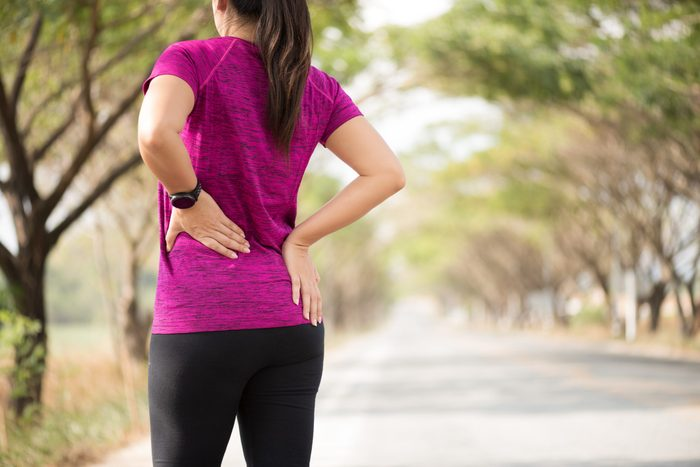 hip pain running   woman clutching painful hip while running