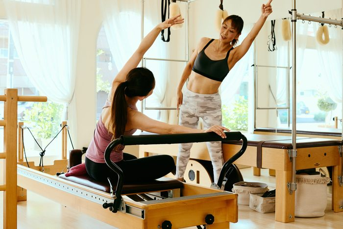 pilates benefits   Senior Woman Pilates Instructor Leading Class On Pilates Reformers In Fitness Studio