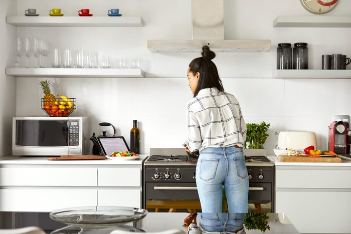 Woman Cooking Food While Looking At Digital Tablet