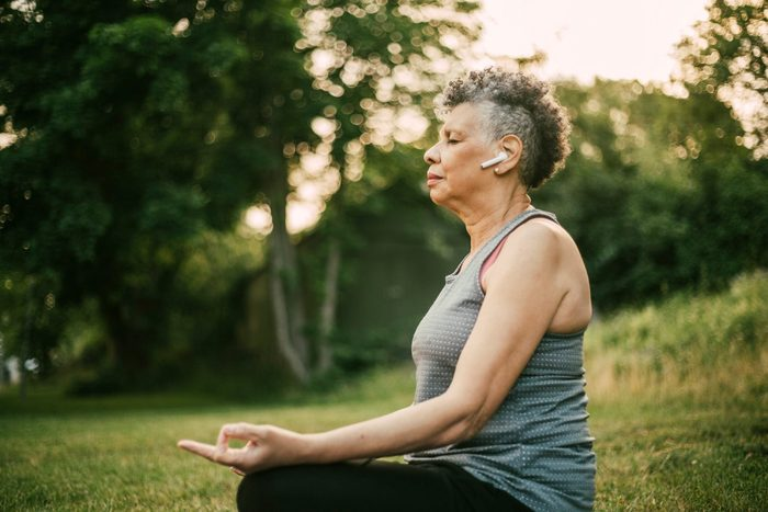 Side View Of Senior Woman With In Ear Headphones Sitting In Lotus Position At Park