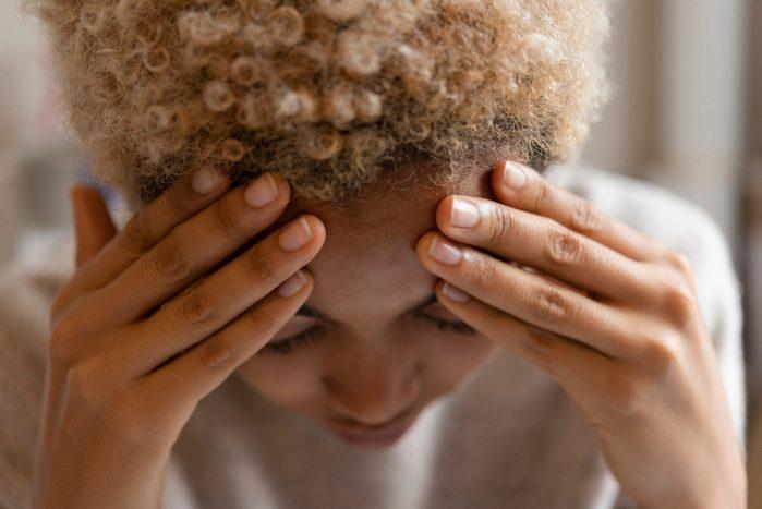 migraine triggers   Woman With Headache Rubbing Forehead