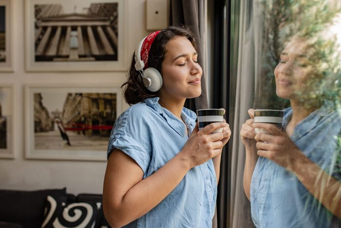 mental health podcast   Portrait Of A Young Woman Standing By The Window And Holding A Cup Of Coffee