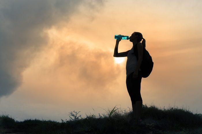 Female,hiker,drinking,bottle,of,water.