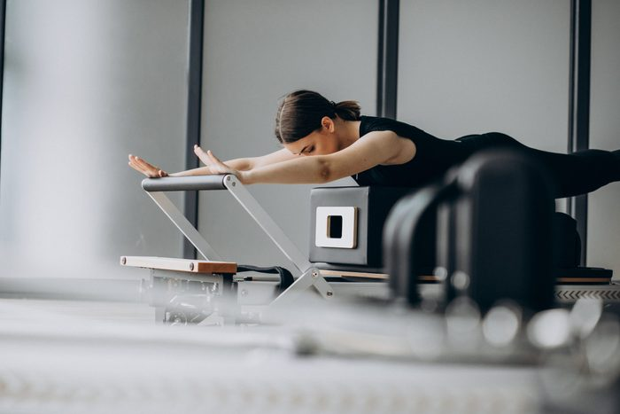 pilates reformer | woman using a pilates reformer at the gym