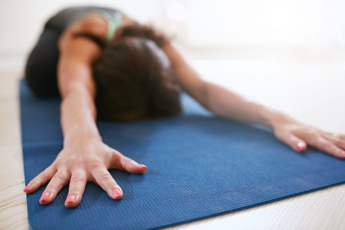 Woman,stretching,forward,,performing,a,yoga,pose,on,exercise,mat.