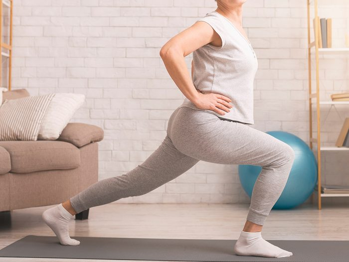 Legs,stretching.,sporty,senior,lady,doing,lunges,at,home,,empty