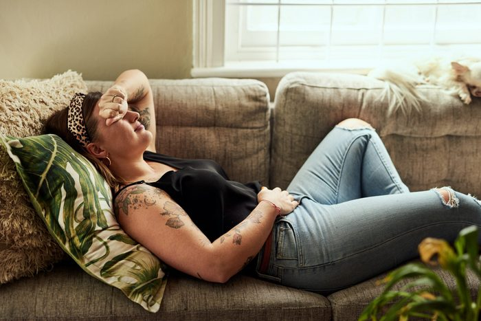 menstrual migraines   woman with menstrual migraines laying on the couch