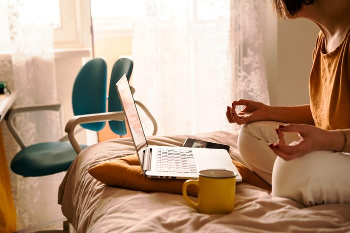 A Middle Aged Woman In White Jeans And A Yellow Sweater Sitting On The Bed In A Yoga Pose In Front Of A Laptop And A Cup Of Coffee