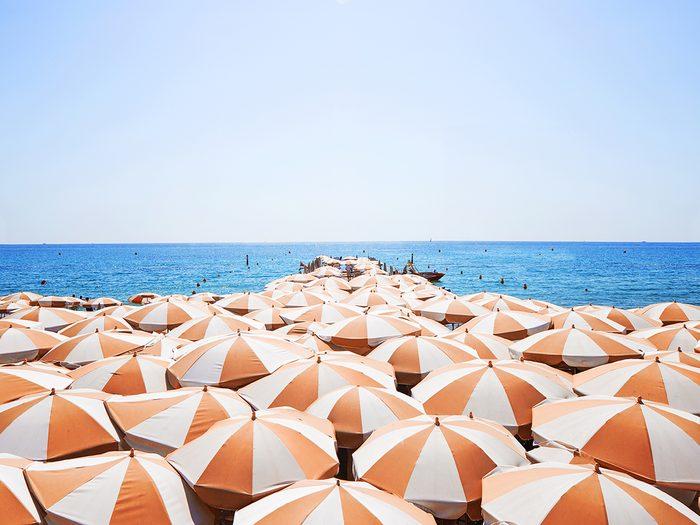 sun care tips   A,lot,of,orange,white,sun,umbrellas,on,a,beach,