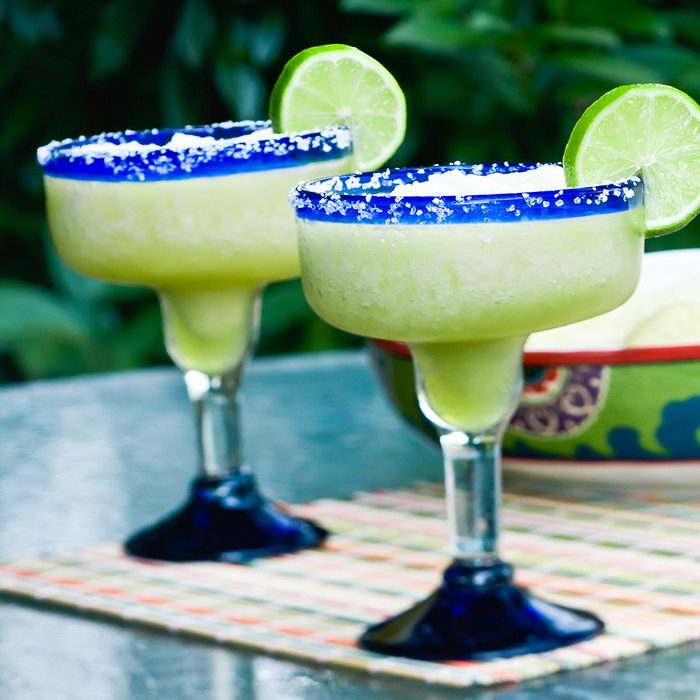 how to make frozen drinks Two frozen lime margaritas with chips and salsa in the background.
