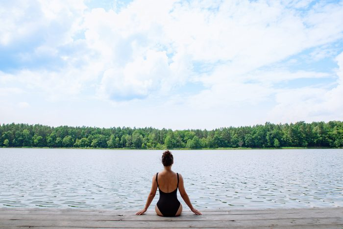 Woman,sitting,on,wooden,dock,looking,at,lake,in,sunny