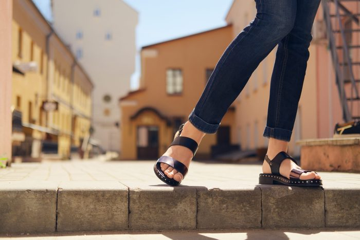womens sandals canada   someone wearing comfortable sandals standing on a ledge