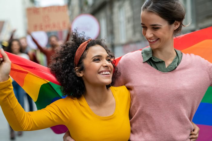 lgbtq2s+ canadians to follow | two people at a pride parade, holding a pride flag together